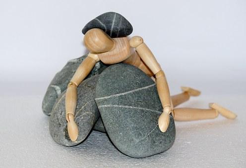 Un ninot articulat de fusta estirat sobre un munt de pedres i amb una pedra al damunt