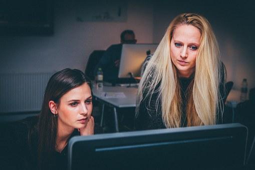 Dos noies davant d'un ordinador