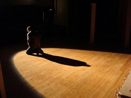 Un actor en mig d'un escenari on es projecta la seva ombra