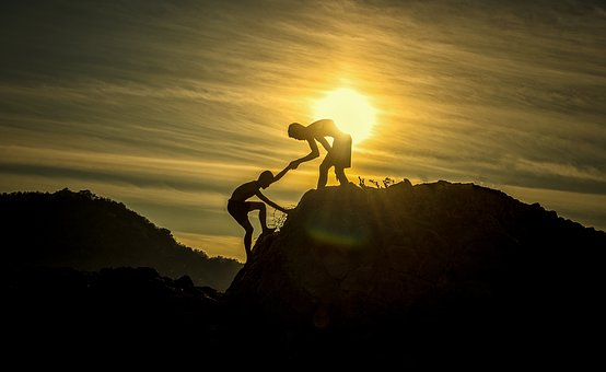 Una persona ajudant una altra a pujar una muntanya