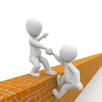 Un ninot que ajuda a pujar un mur a un altre