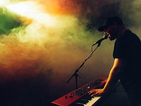 Músic cantant i tocant el teclat en un concert