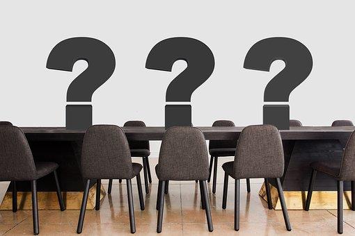 Taula amb cadires i 3 interrogants en alguns llocs
