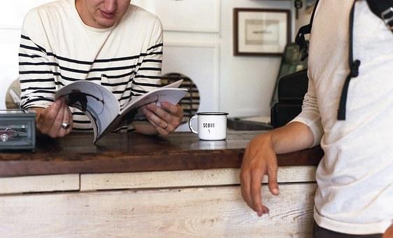 Una persona recolzada en un taulell llegint i un altre al costat