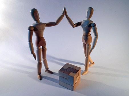 Dos figures articulades que xoquen la mà