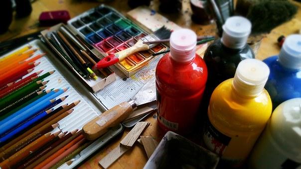 Taula amb llapis de colors i pintures i pinzells diversos