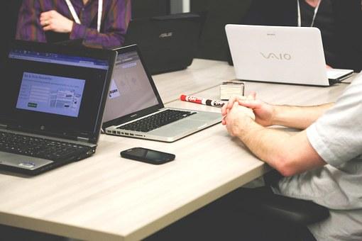 Taula amb persones treballant amb ordinadors