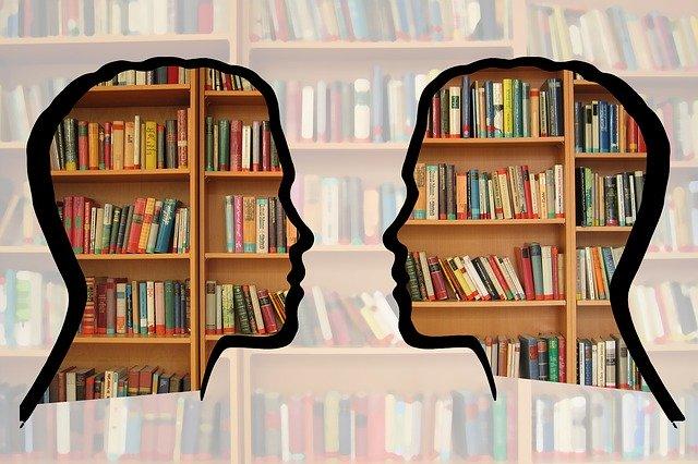 Una biblioteca amb dos siluetes de cap transparents superposades