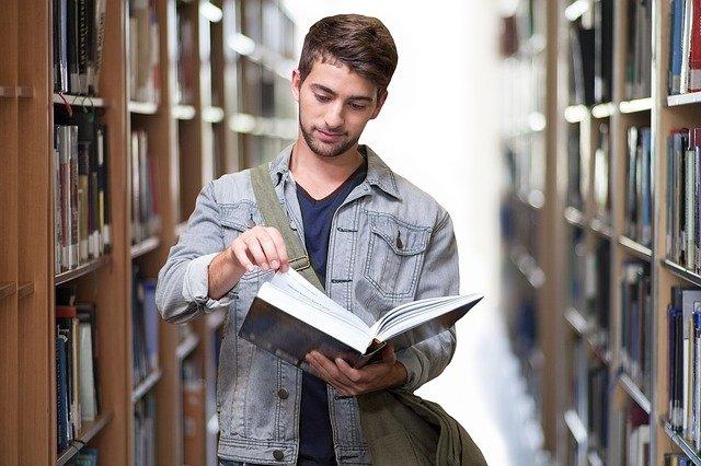 Estudiant fullejant un llibre entre les estanteries d'una biblioteca