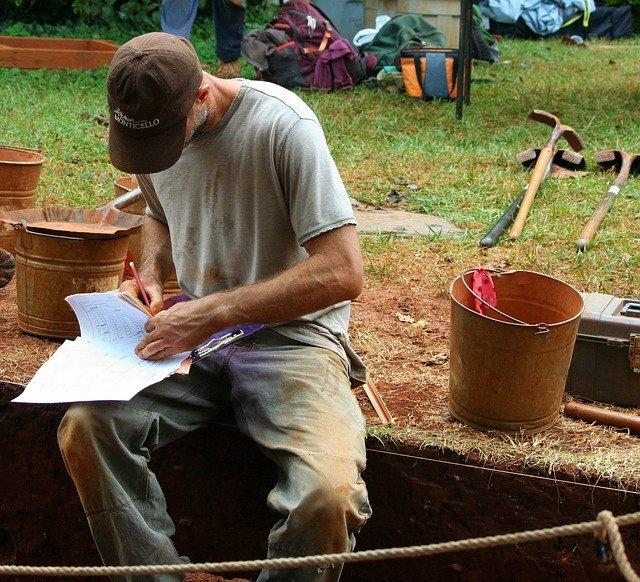 Un arqueòleg en un jaciment arqueològic, anotant quelcom en una llibreta