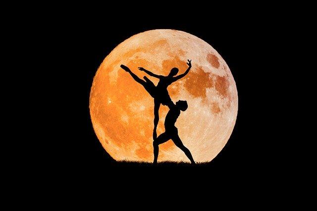Sobre el fons de la lluna plena es veu la situeta d'una parella de ballerins classics