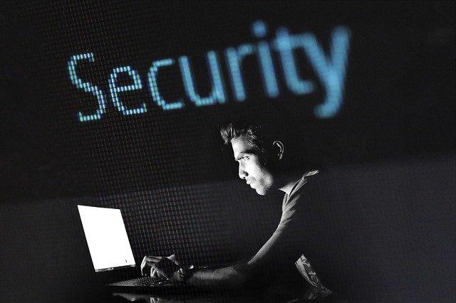 Persona amb ordinador a les fosques i amb un cartell lluminós de Security
