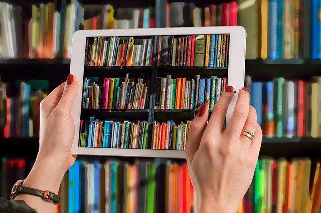 Una tauleta fotografiant llibres d'una biblioteca