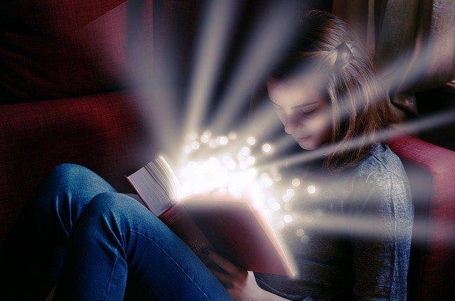 Noia llegint un llibre del qual surten espurnes de llum
