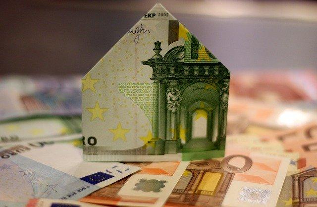 Un billet doblegat en forma de casa sobre molts bitllets