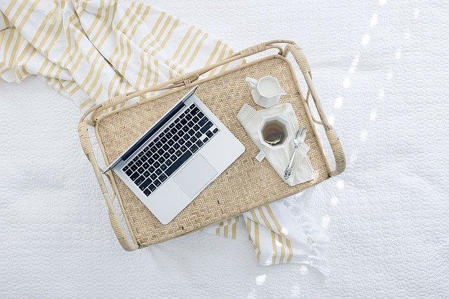 Una plata amb un cafè amb llet i un ordinador
