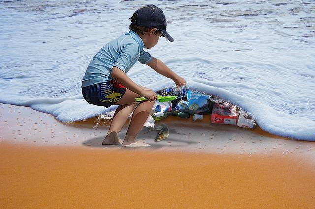 Un nen aixeca una ola del mar com si fos un llençol i a sota hi ha molts residus plàstics