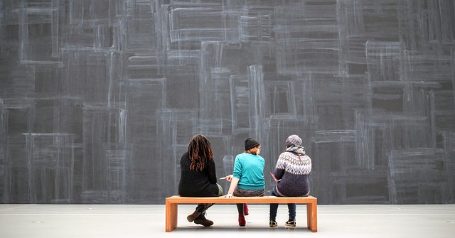 3 persones assegudes en un banc observant una obra d'art