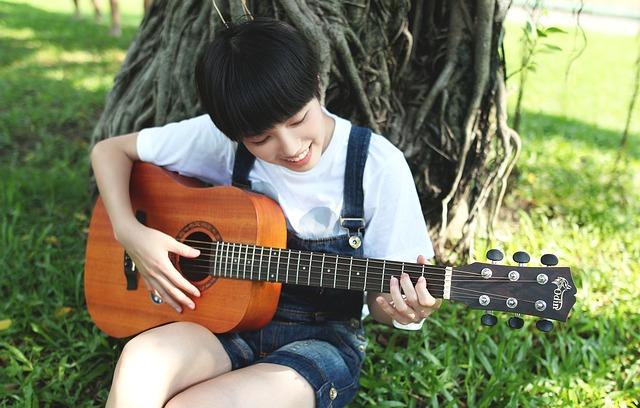 Jove tocant la guitarra recolzada en un arbre