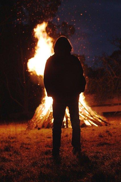 Persona davant d'una foguera en la foscor de la nit