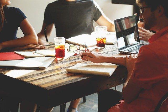 3 persones treballant al voltant d'una taula