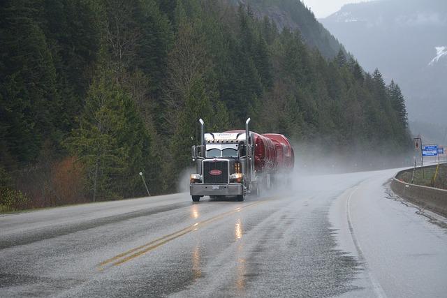 Camió cisterna que avança per una carretera local amb el fer mullat