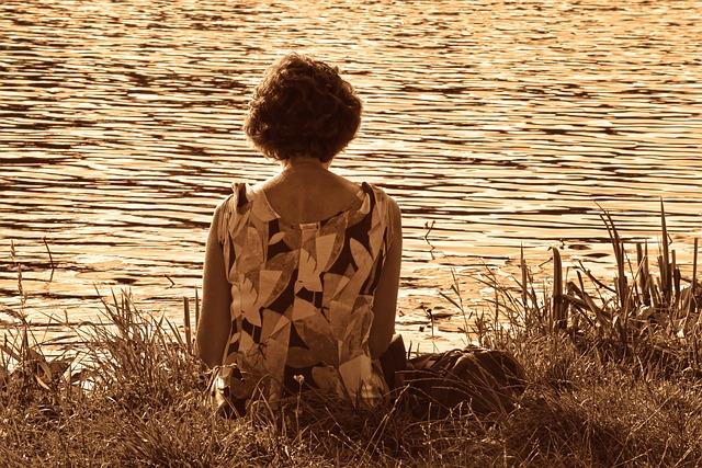 Dona d'esquena sentada en la riba del riu