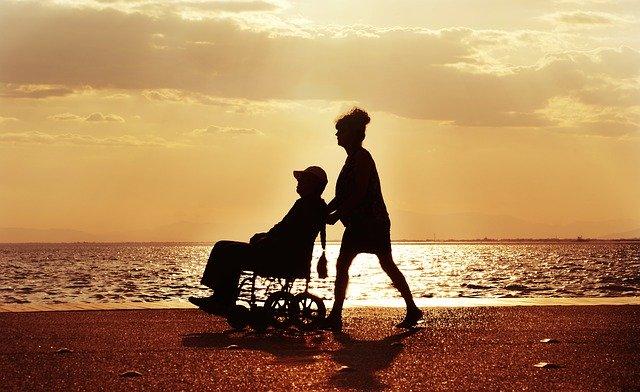 Senyora portant a persona amb cadira de rodes prop del mar