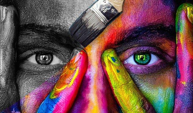 Una cara pintada de colors amb una brotxa