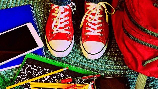 Sabatilles convers vermelles, motxilla, llibretes, llapis i un mòvil