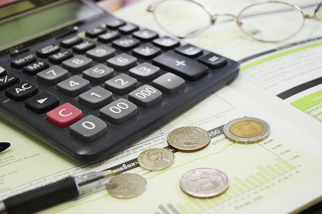 Calculadora, papers, ulleres, bolìgraf i monedes