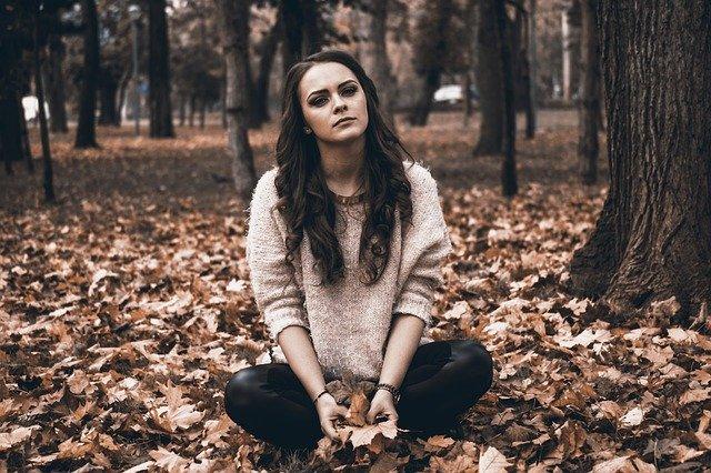 Noia en un bosc, asseguda damunt de fulles seques