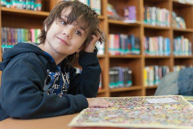 Nen somniant mentre mira un conte en una biblioteca
