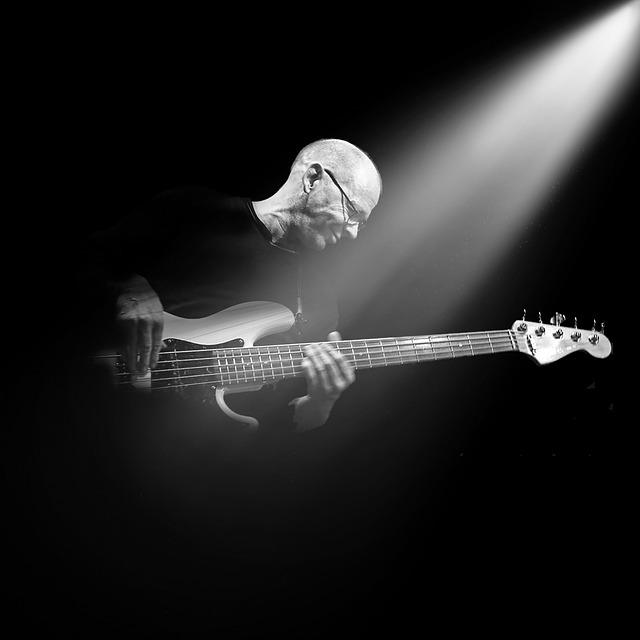 Intérpret tocant la guitarra il·luminat per un focus de llum
