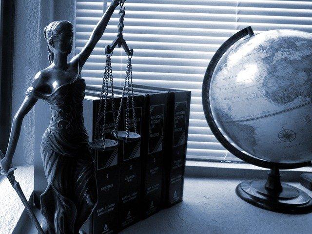 Un escriptori amb llibres de dret, bola del món i la Justícia amb la balança a una mà i l'espasa a l'altra