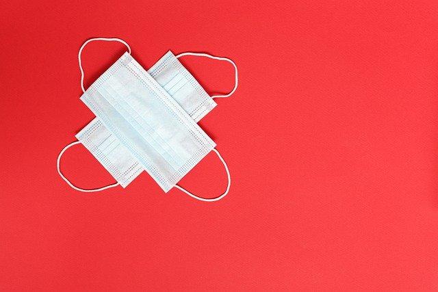 Dues mascaretes en forma de creu sobre un fons vermell