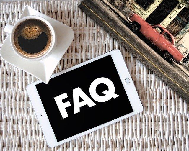 Una plata amb una taça de cafè i un mòbil amb la paraula FAQ