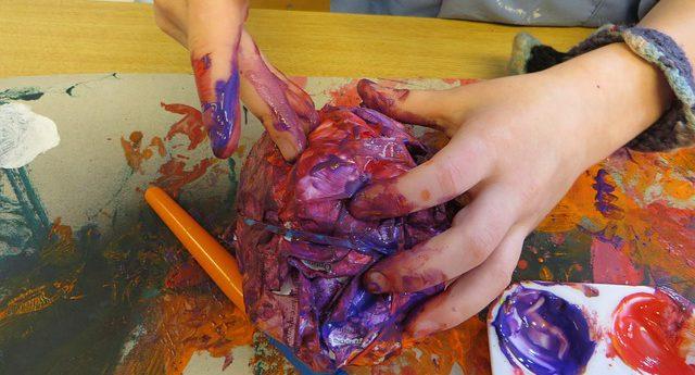 Mans d'un nen que pinta i modela